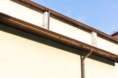 Alloggi la parete con la grondaia ed il tubo di scarico sul fondo del cielo blu Fotografia Stock Libera da Diritti