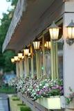 Alloggi la parete con le lampade ed i fiori di una petunia Fotografia Stock