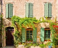 Alloggi la parte anteriore con le finestre con le imposte e la facciata frondosa, Provenza, Francia fotografie stock