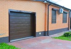Alloggi la porta del garage con ventilazione, il condizionatore d'aria, il sistema di conduttura della grondaia della pioggia, gl Fotografie Stock