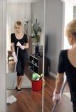 Alloggi la pulizia, donna sta passando lo straccio sul pavimento di legno Fotografia Stock