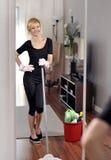 Alloggi la pulizia, donna sta passando lo straccio sul pavimento di legno Immagine Stock