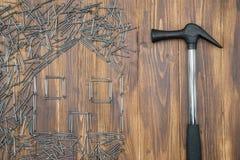 Alloggi la riparazione, forma della casa dal gruppo di chiodo con il martello Fotografie Stock Libere da Diritti