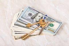 Alloggi le chiavi che si trovano sopra il mucchio delle banconote del dollaro Fotografia Stock