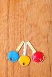 Alloggi le chiavi con i cappucci variopinti dei cappotti della plastica sulla tavola Immagini Stock