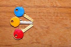 Alloggi le chiavi con i cappucci variopinti dei cappotti della plastica sulla tavola Fotografie Stock Libere da Diritti