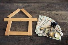 Alloggi le chiavi sopra le cento banconote del dollaro contro fondo di legno Immagine Stock