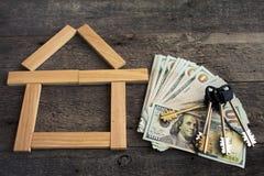Alloggi le chiavi sopra le cento banconote del dollaro contro fondo di legno Fotografia Stock