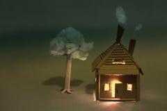 Alloggio con le finestre luminose, albero di carta del cartone Tempo di sera Fotografie Stock