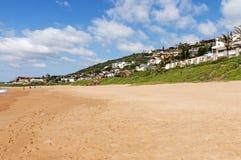 Alloggio residenziale della sabbia della vegetazione della duna e cielo blu nuvoloso Fotografia Stock