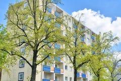 Alloggio sociale dietro alcuni alberi Immagine Stock