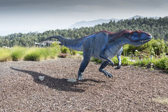 Allosaurus dinosaur. Running in the middle of a forest royalty free stock image