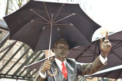 `Allow Me` Statue in Portland, Oregon 2. This is the `Allow Me` statue in Portland, Oregon`s Pioneer Square.  A man in a business suit holding an umbrella Stock Photography