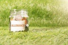 Allowance money, coins in glass jar for money saving financial concept stock photos