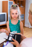 Allowance of pocket money. Cute little girl and mother with purse at home Royalty Free Stock Photography