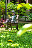 Alloy Children reading book on chair in home garden. Royalty Free Stock Photos