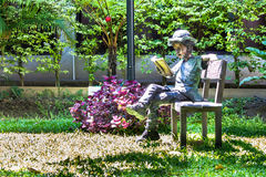 Alloy Children reading book on chair in home garden. Alloy Children reading book on chair in home garden on summer Royalty Free Stock Image