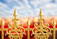 Alloy fence. Row of the golden alloy fence on blue sky background Stock Photo