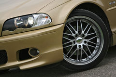 Alloy wheel on golden sports car. A golden sports car with an alloy wheel, posing on a tarmac royalty free stock images