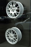 Alloy wheels. In shop window with cars reflected on glass in background Royalty Free Stock Image