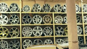 Alloy wheels in the store on the shelves. The camera moves from left to right. The discs are different and new Stock Image