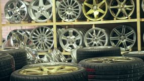 Alloy wheels in the store on the shelves. The camera moves from left to right. The discs are different and new Royalty Free Stock Photography