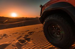 Allradfahrzeug, Wüste und Sonnenuntergang stockfotografie