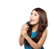Allsång för ung kvinna som rymmer en mic som isoleras Royaltyfria Bilder