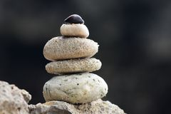 Allsidiga staplade stenar eller kiselstenar på en vit sand sätter på land Arkivfoton