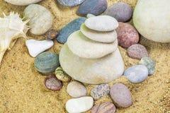 Allsidiga stenar som staplas på sand Royaltyfri Fotografi