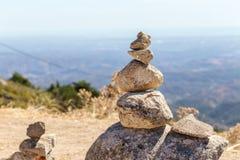 Allsidiga stenar står i kulle med en sikt av Algarven Portugal Arkivfoto