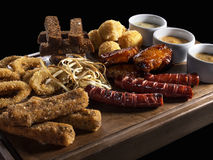 Allsorts of meat, chicken fish snacks isolated on black. Allsorts fried snacks with three different sauces on wooden board close-up isolated on black background royalty free stock images