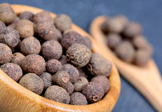 Allspice in a bamboo bowl. On slate royalty free stock image