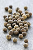 Allspice berries. Several dry whole allspice berries on wooden background stock image