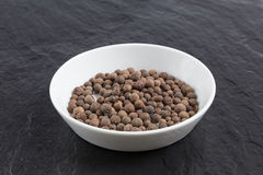 Allspice in a bowl on a slate Stock Photos