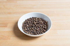 Allspice in a bowl on wood Royalty Free Stock Images