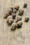 Allspice close-up. Close-up of allspice peppercorns on wooden background stock photography