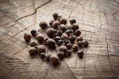 Allspice. Fragrant black pepper on wooden background Royalty Free Stock Image