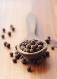 Allspice grains. Allspice pepper on an old wooden spoon royalty free stock images
