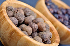 Allspice with juniper in a bamboo bowls. On slate royalty free stock photo