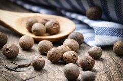 Allspice pepper. On the rustic wooden table Stock Photos