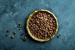 Allspice pepper, peppercorns on dark culinary background, top view royalty free stock image