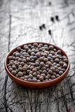 Allspice. Peppercorns in a bowl on a vintage wooden table Royalty Free Stock Image