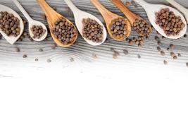 Allspice. Photo of spoons with allspice seeds on wooden board with white space for text stock photos