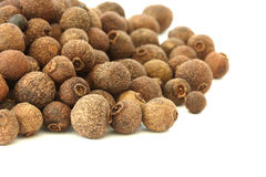 Allspice - pimento - on white background. Scattered allspice - pimento spice on white background - macro view Stock Images