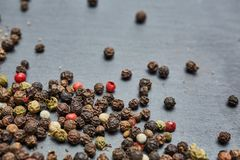 Allspice seeds on dark background, shallow depth of field. Allspice seeds on dark background. Heap of spice. Mix of different peppers. Top view, macro, shallow stock photo