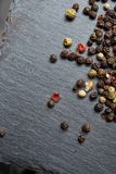 Allspice seeds isolated on dark background, shallow depth of field. Allspice seeds isolated on dark background. Heap of spice. Mix of different peppers. Top Stock Images