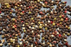 Allspice seeds isolated on dark background, shallow depth of field. Allspice seeds isolated on dark background. Heap of spice. Mix of different peppers. Top stock photography