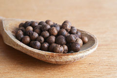 Allspice in spoon. Allspice grain in spoon on wooden background stock images
