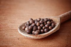 Allspice in spoon. Allspice grain in spoon on wooden background stock photos